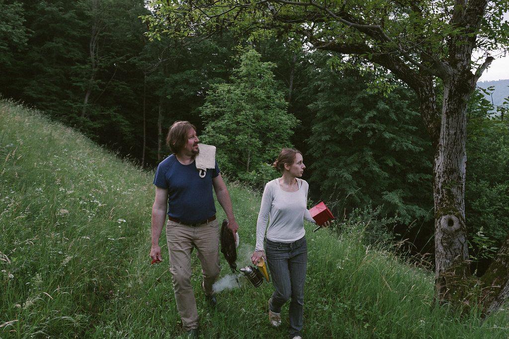 Die Bioimker: Thomas Waitz und Helene Polak gehen am Eichberg zu ihren Bienen, mit Bienenschleier, Smoker und Stockkarten-Box in der Hand.